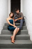 image of office romance  - Happy young couple sitting on the steps in office - JPG