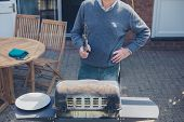 foto of braai  - A senior man is attending to a barbecue in the garden on a sunny day - JPG