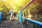 stock photo of cave woman  - young asian woman hiker climbing on stone stairs to mountain peak - JPG