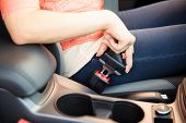 image of seatbelt  - Closeup of a young woman buckling up her seatbelt before driving her car - JPG