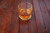 pic of tumbler  - Tumbler glass full of whisky standing on a wooden table - JPG