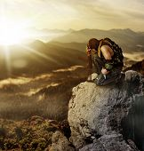 image of morning  - Military man warrior praying before the fight and sitting on a rock on summer morning - JPG