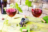 pic of grape  - Two glasses of red wine on the background of an old brick wall and grape vines - JPG