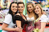 pic of funfair  - Joyful young and attractive women at German funfair Oktoberfest with traditional dirndl dresses and joyride in the background - JPG