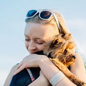 pic of dog eye  - beautiful young happy woman with blonde hair blink her eyes and holding small dog - JPG