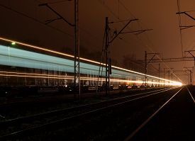 picture of passenger train  - POLAND. LODZ. December 11, 2013 Passenger train while driving at night and stationary freight train. - JPG