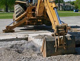 foto of backhoe  - dust flies as a backhoe bucket lifts a slab of concrete from the roadway - JPG