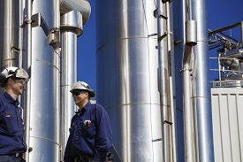 stock photo of pipeline  - oil and gas workers with giant giant gas - JPG