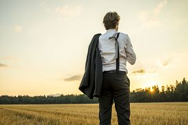 foto of stressless  - Young successful businessman standing in wheat field looking gazing into the future as he decides upon new steps and directions to take in his career - JPG
