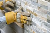 Closeup Of Manual Worker In Protection Gloves Pushing The Tile Into The Cement On The Wall poster