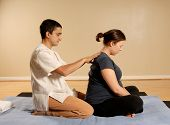 stock photo of thai massage  - therapist giving a thai massage to pregnant woman - JPG