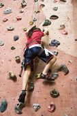 stock photo of climbing wall  - a young girl climbing a tall indoor man - JPG