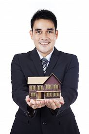 stock photo of house representatives  - Portrait of young businessman showing a hous model representing home ownership and the real estate business - JPG