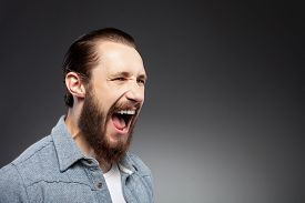 image of irritated  - Attractive bearded hipster guy is showing his aggression - JPG
