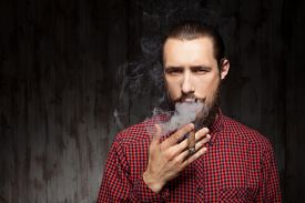 stock photo of smoke  - Cheerful hipster guy with beard is smoking with relaxation - JPG