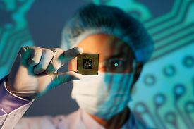 pic of microchips  - Image of an electronic engineer analyzing computer microchip holding on the foreground - JPG