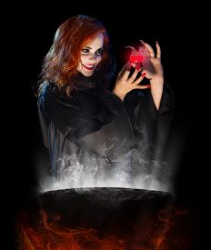 stock photo of cauldron  - Young witch with red potion and cauldron isolated - JPG