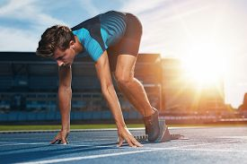 picture of sprinters  - Young male runner taking ready to start position against bright sunlight - JPG