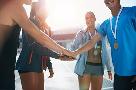 stock photo of huddle  - Shot of a group of young sportsmen with medals piling their hands while standing in a huddle - JPG