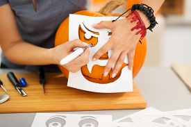 picture of carving  - Closeup on woman using stencils to carve big orange pumpkin Jack - JPG