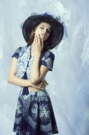 stock photo of up-skirt  - summer fashion shoot of cute female in romantic pose with hat and elegant skirt and top long hair natural make - JPG