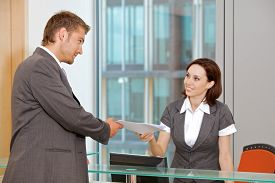 picture of secretary  - Young caucassian secretary assisting businessman - JPG