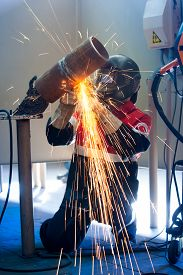 pic of pipe-welding  - Welder working in the red uniform and a mask - JPG