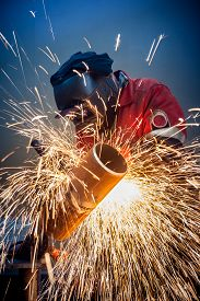 foto of pipe-welding  - Welder working in the red uniform and a mask - JPG