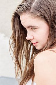 stock photo of sarcastic  - Beautiful young brunette woman with green eyes standing in profile and looking sarcastic - JPG