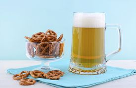 stock photo of stein  - Glass of beer in stein with mini pretzels on pale blue napkin on pale blue and white wood background - JPG