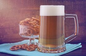 stock photo of stein  - Glass of beer in stein with mini pretzels on pale blue napkin on wood background with added retro vintage style filters and lens flare sun stream - JPG