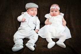stock photo of christening  - Twin babies dressed up for christening day - JPG