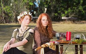 image of sabbatical  - Two serious pagan females sitting at altar with candles - JPG