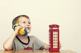 image of phone-booth  - Little cheerful boy talking on the phone and vintage british red telephone booth - JPG
