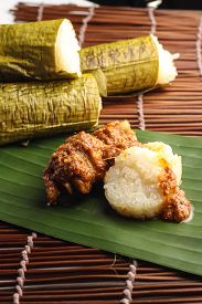 picture of malay  - malay lemang served with rendang ayam on wooden background - JPG