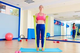 picture of rubber band  - Pilates woman biceps rubber band exercise workout at gym indoor - JPG