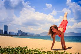 stock photo of short legs  - blond slim girl in short red frock stands in gymnastic position hands leg scale on sand beach against azure sea and city - JPG