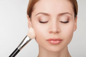 stock photo of face-powder  - Skilled beautician is applying powder on face of model - JPG