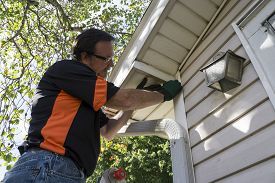 foto of soffit  - Contractor fixing vinyl siding on a customers home - JPG