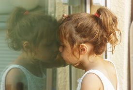 foto of thoughtfulness  - Thoughtful little girl looking through the window - JPG
