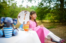 foto of alice wonderland  - Girl sits at table and holding a cup of tea - JPG