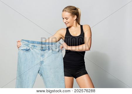 poster of diet, weight loss and people concept - young slim sporty woman with oversize pants