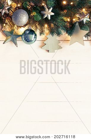 poster of White Wooden Background With Copy Space. Vertical Christmas Banner With Turquoise Christmas Decoration Like Balls, Tree And Star. Fir Branches With Fairy Lights And Instagram Filter.