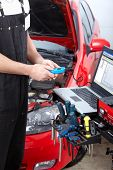 stock photo of car repair shop  - Handsome mechanic working in auto repair shop - JPG