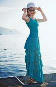Young woman in blue dress standing at the moorage.