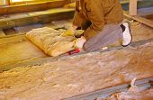 stock photo of glass-wool  - Construction worker thermally insulating house attic with glass wool - JPG