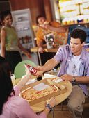 stock photo of pizza parlor  - Young man passing cell phone in pizza parlor - JPG