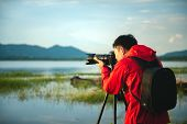 Travel Photographer Taking A Photo With Nature The Lake In Sunset With Camera On Tripod, Focusing At poster