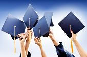 stock photo of throw up  - Group of people throwing graduation hats in the air - JPG