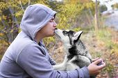 Man Kisses  Dog (puppy) Of The Breed Siberian Husky. Dog Training And Obedience poster